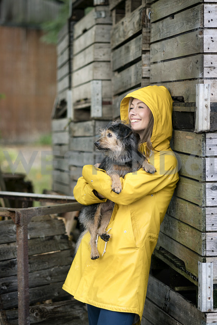 Smiling woman on a farm standing at wooden boxes holding dog - PESF00956 - Peter Scholl/Westend61
