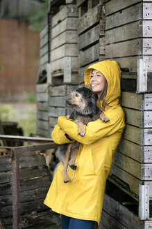 Smiling woman on a farm standing at wooden boxes holding dog - PESF00956