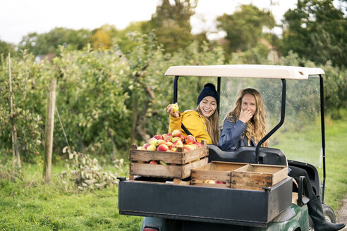 Two women with vehicle harvesting apples in orchard - PESF00959