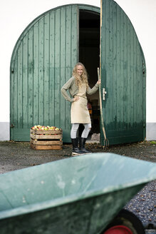 Smiling woman on a farm standing at crate with apples - PESF00968
