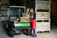 Two women using laptop between crates on a farm - PESF00980