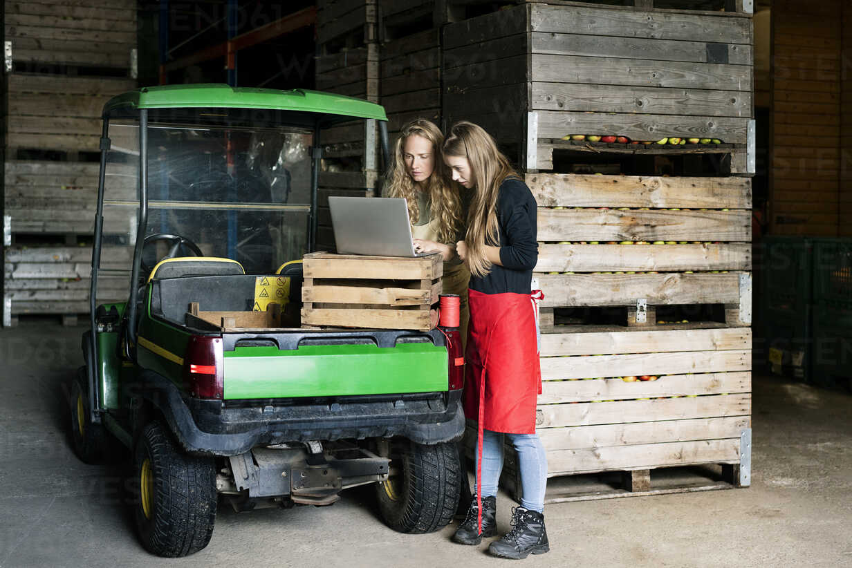 Two women using laptop between crates on a farm - PESF00980 - Peter Scholl/Westend61