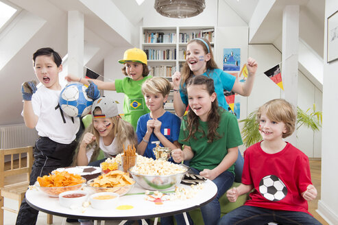 Group of kids watching soccer world championship with table full of sweets and snacks - NEKF00020