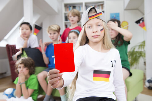 Girl showing red card in front of friends, watching football world cup - NEKF00026