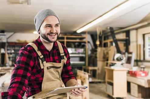 Smiling worker holding tablet in workshop - UUF12668