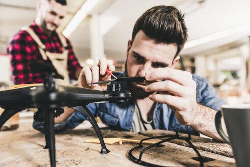 Man working on drone in workshop - UUF12680