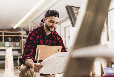 Worker looking at draft in workshop - UUF12689