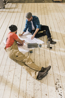Two men with laptop looking at construction plan on the floor - UUF12692