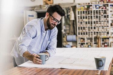 Smiling man looking at construction plan - UUF12719