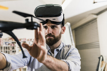 Man wearing VR glasses holding drone - UUF12722