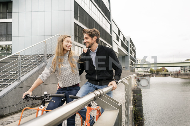 Smiling couple with bicycles in the city - PESF00991 - Peter Scholl/Westend61