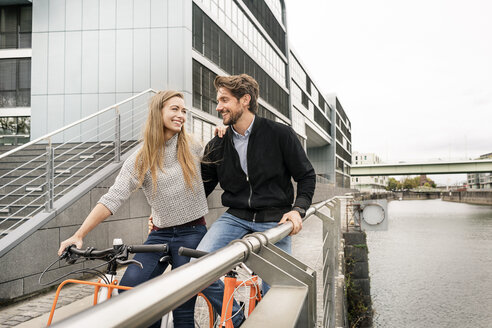 Smiling couple with bicycles in the city - PESF00991