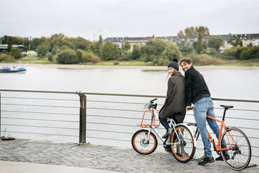 Smiling couple with bicycles at the riverside - PESF01003