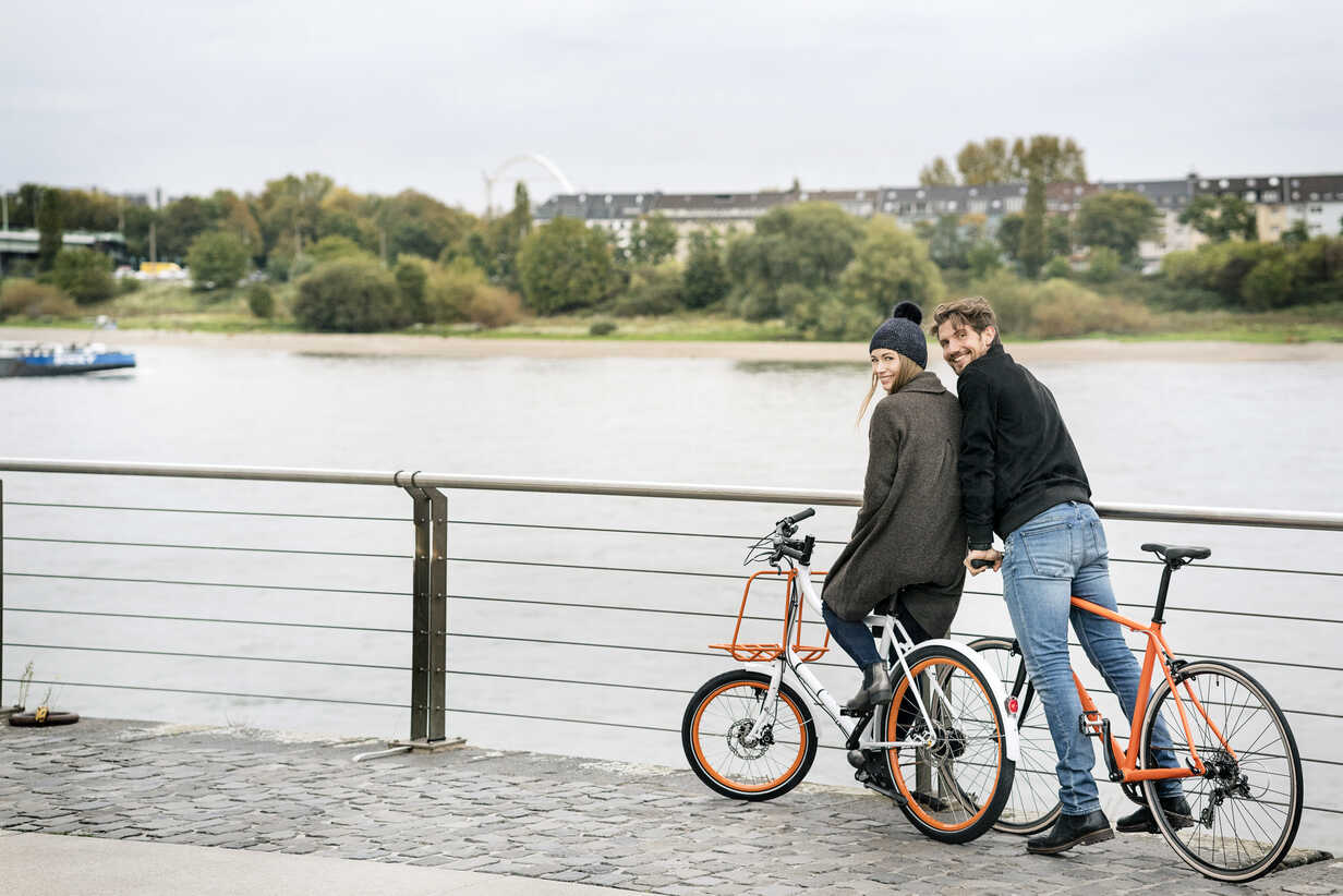 Smiling couple with bicycles at the riverside - PESF01003 - Peter Scholl/Westend61