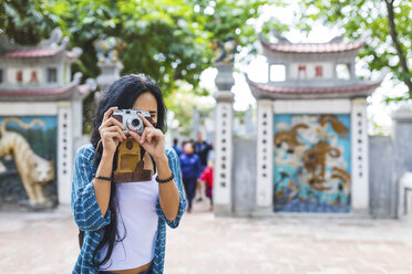 Vietnam, Hanoi, young woman taking a picture with old-fashioned camera - WPEF00049
