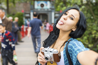 Vietnam, Hanoi, young woman with an old-fashioned camera sticking her tongue out - WPEF00052