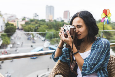 Vietnam, Hanoi, young woman taking a picture with old-fashioned camera - WPEF00055