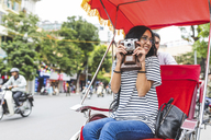 Vietnam, Hanoi, young woman with old-fashioned camera on a riksha - WPEF00058