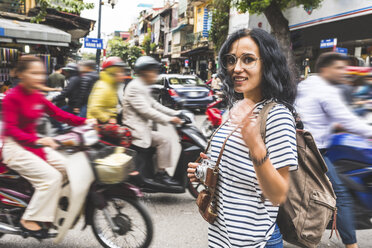 Vietnam, Hanoi, portrait of smiling young woman amidst traffic in the city - WPEF00061