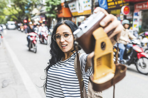 Vietnam, Hanoi, young woman taking a selfie with old-fashioned camera on the street - WPEF00064
