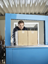 Worker watching machine closing packages - CVF00109