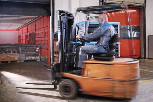 Fork-lift driver loading lorry - CVF00112