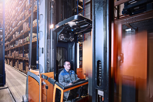 Worker operating high rack in storehouse - CVF00121
