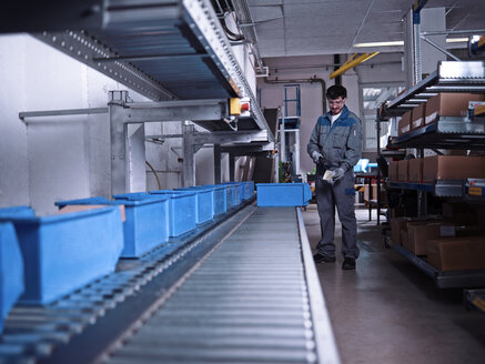 Worker scanning merchandise at conveyor belt - CVF00127