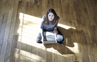 Portrait of young woman using laptop on wooden floor - FMKF04808