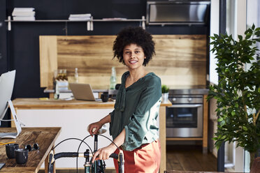 Portrait of smiling young woman with bicycle in modern office - FMKF04814