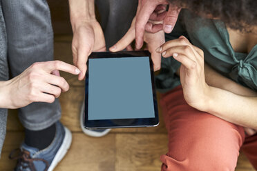 Four people sharing tablet - FMKF04838
