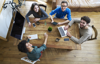 Elevated view of smiling coworkers working together at wooden table in office - FMKF04841