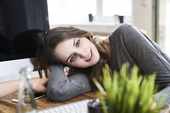Portrait of smiling young woman leaning on desk in office - FMKF04844