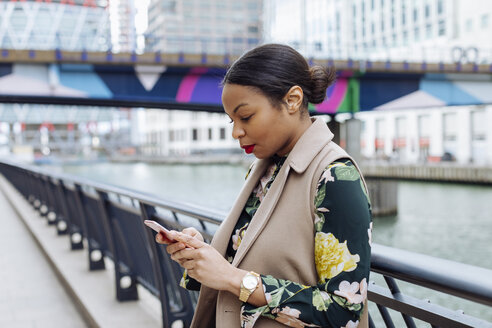 UK, London, fashionable  businesswoman using smartphone - MAUF01312