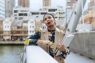 UK, London, portrait of fashionable  businesswoman leaning on railing of bridge - MAUF01318
