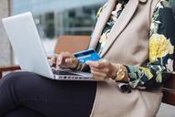 Businesswoman sitting on bench using laptop and credit card, partial view - MAUF01324