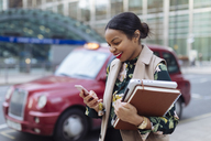 UK, London, happy businesswoman looking at cell phone - MAUF01327