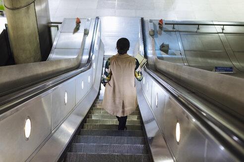 Back view of businesswoman standing on escalator of underground station - MAUF01330