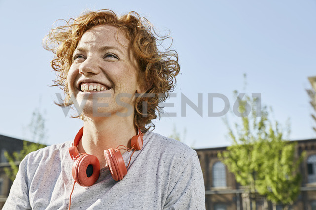 Portrait of happy young woman with headphones in urban surrounding - PDF01419 - Philipp Dimitri/Westend61