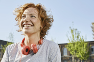 Portrait of happy young woman with headphones in urban surrounding - PDF01419