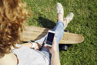 Young woman with smartwatch and longboard using smartphone on meadow - PDF01425