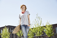 Smiling young woman with longboard, headphones and smartwatch standing in urban surrounding - PDF01428