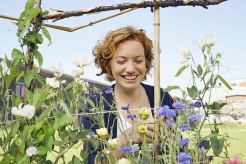Smiling young woman urban gardening - PDF01431
