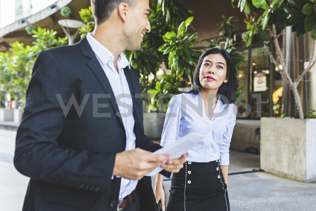 Thailand, Bangkok, smiling businessman and businesswoman with documents talking in the city - WPEF00066