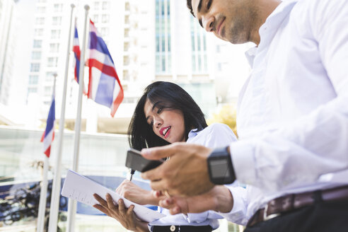 Thailand, Bangkok, businessman and businesswoman in the city with documents, cell phone and smartwatch - WPEF00072