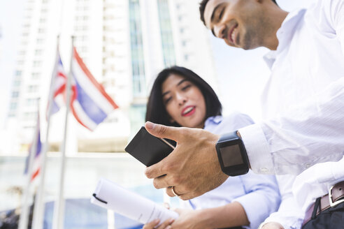 Thailand, Bangkok, businessman and businesswoman in the city with cell phone and smartwatch - WPEF00075