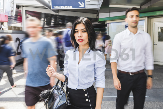 Thailand, Bangkok, portrait of businesswoman amidst moving people in the city - WPEF00081
