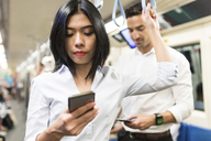 Businessman and businesswoman using cell phones in the subway - WPEF00084