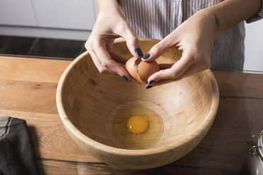 Woman breaking egg, wooden bowl - MAUF01331