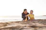 Mother playing with little daughter on the beach - DIGF03237